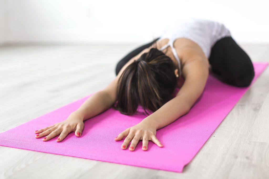 En flicka som gör yoga på en yogamatta